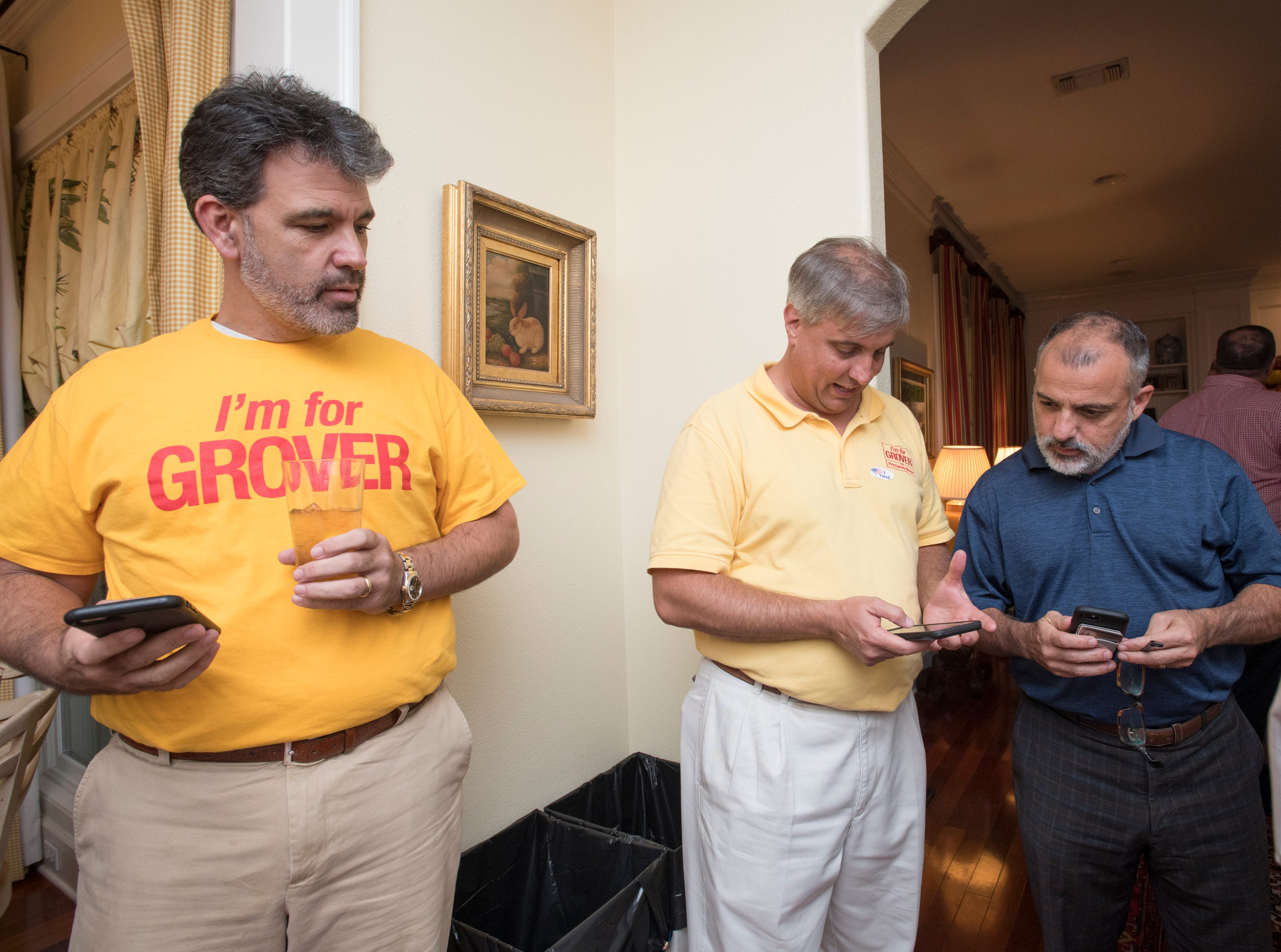 Brett Parra, from left, Grover Robinson, and Michael Carro check the Penscola Mayoral race returns on Election Night in Pensacola on Tuesday, November 6, 2018.
