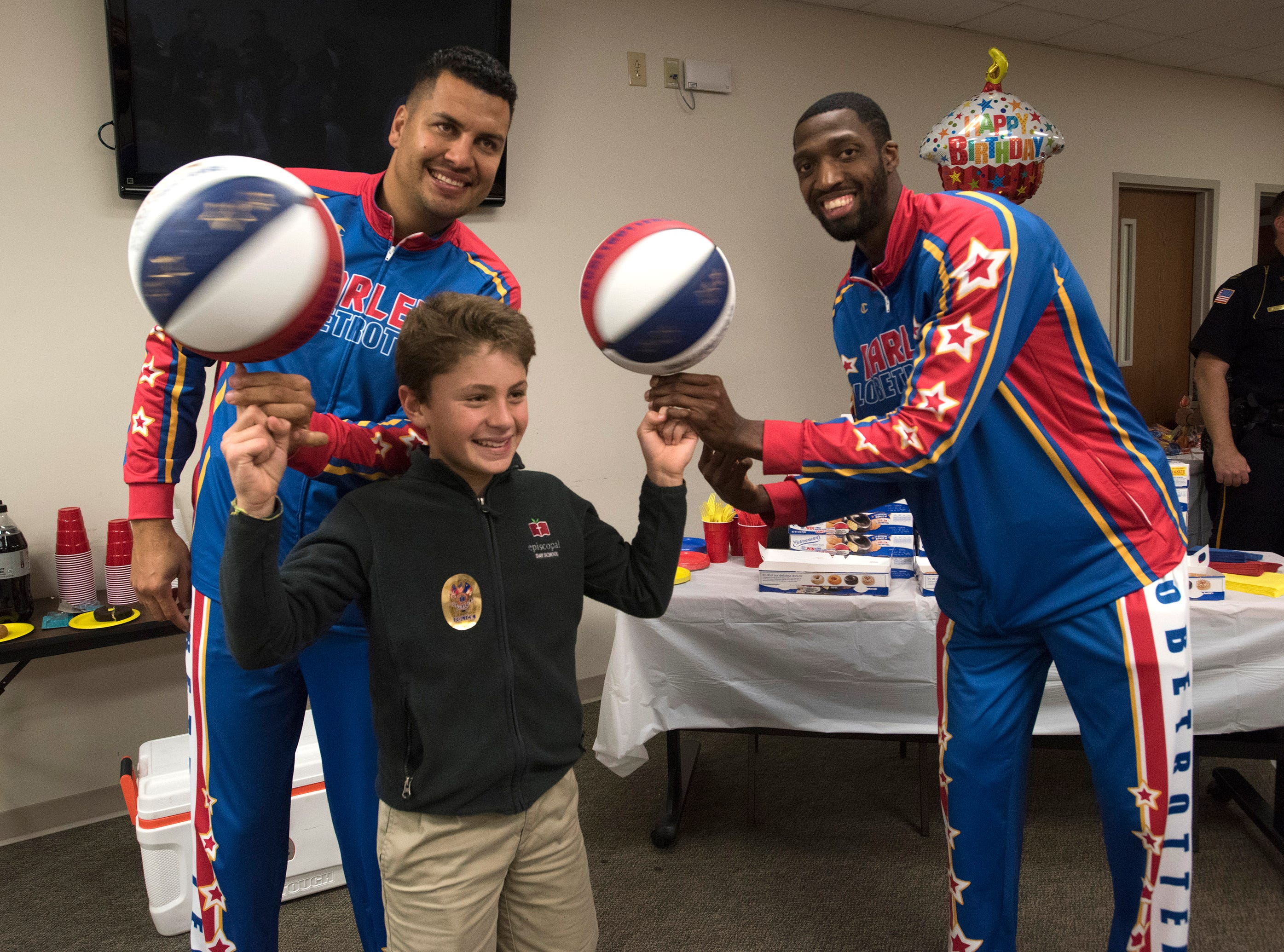 El Gato Melendez, and Bulldog Mack, two members of the Harlem Globetrotters, teach Chad Bonner a few tricks during their visit to the Pensacola Police Department on Wednesday, Nov. 7, 2018.
