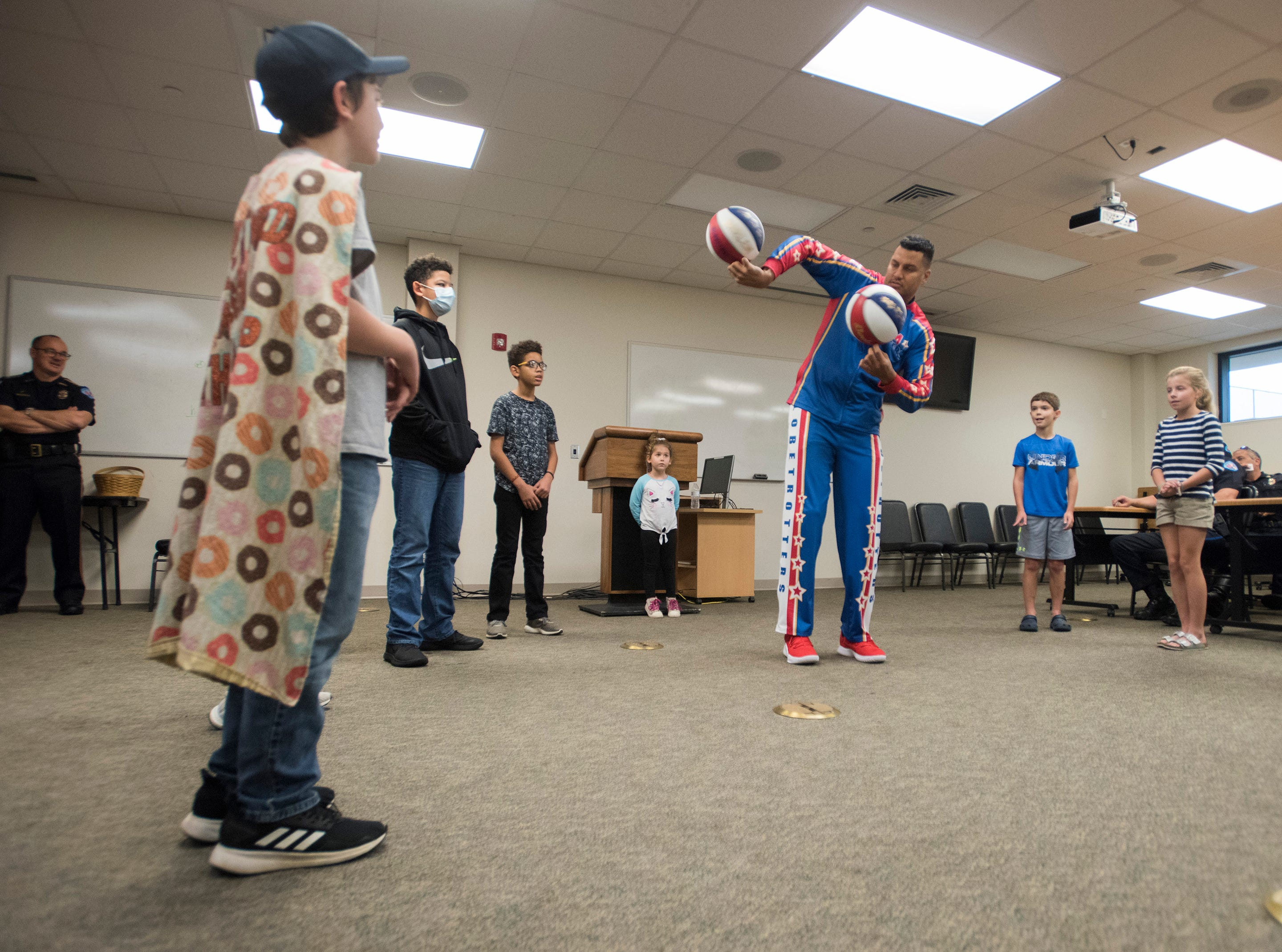 "El Gato Melendez, a member of the Harlem Globetrotters, performs a few tricks as Tyler Carach, left, and a group of children look on during a birthday party for the 11-year old at the Pensacola Police Dept. on Wednesday, Nov. 7, 2018. Carach is also known as the ""donut boy"" and has delivered more than 70,000 of the pastries to law enforcement officersaround the country."