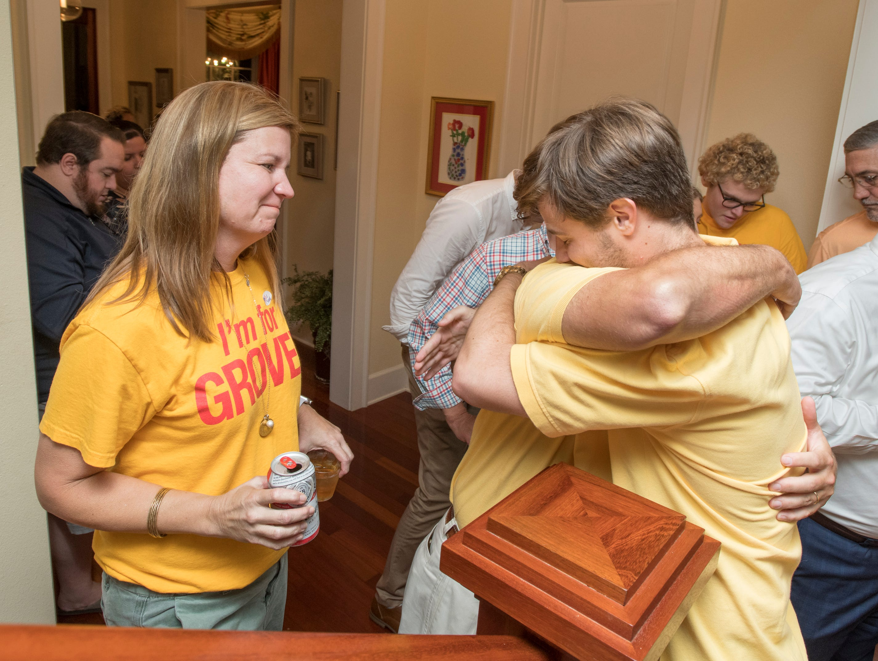 Jill Robinson looks on as her husband Mayor-elect Grover Robinson IV gets a hug from their son Grover V after being declared the winner on Election Night in Pensacola on Tuesday, November 6, 2018.
