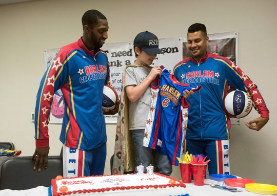 """Bulldog Mack and El Gato Melendez, two members of the Harlem Globetrotters, presents Tyler Carach with a team jersey during a birthday party for the 11-year old at the Pensacola Police Dept. on Wednesday, Nov. 7, 2018. Carach is also known as the """"donut boy"""" and has delivered more than 70,000 of the pastries to law enforcement officers around the country."""