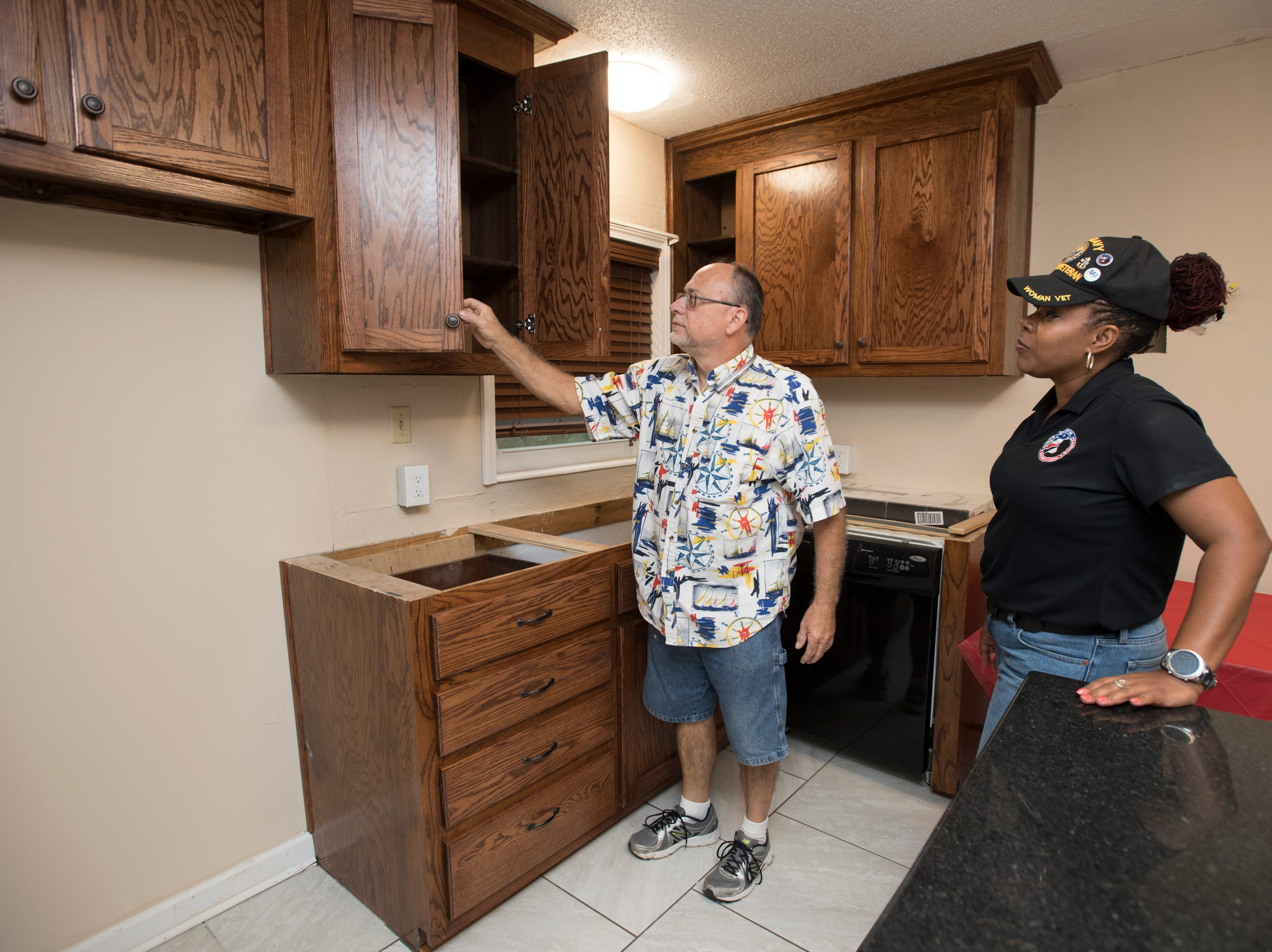 CEO and founder Nancy Bullock-Prevot, right, and Mike Frazier look through the kitchen cabinets at the HER Foundation Faith House on West Fairfield Drive in Pensacola on Wednesday, November 7, 2018.  Frazier donated his craftsmanship to provide the cabinets for the house.