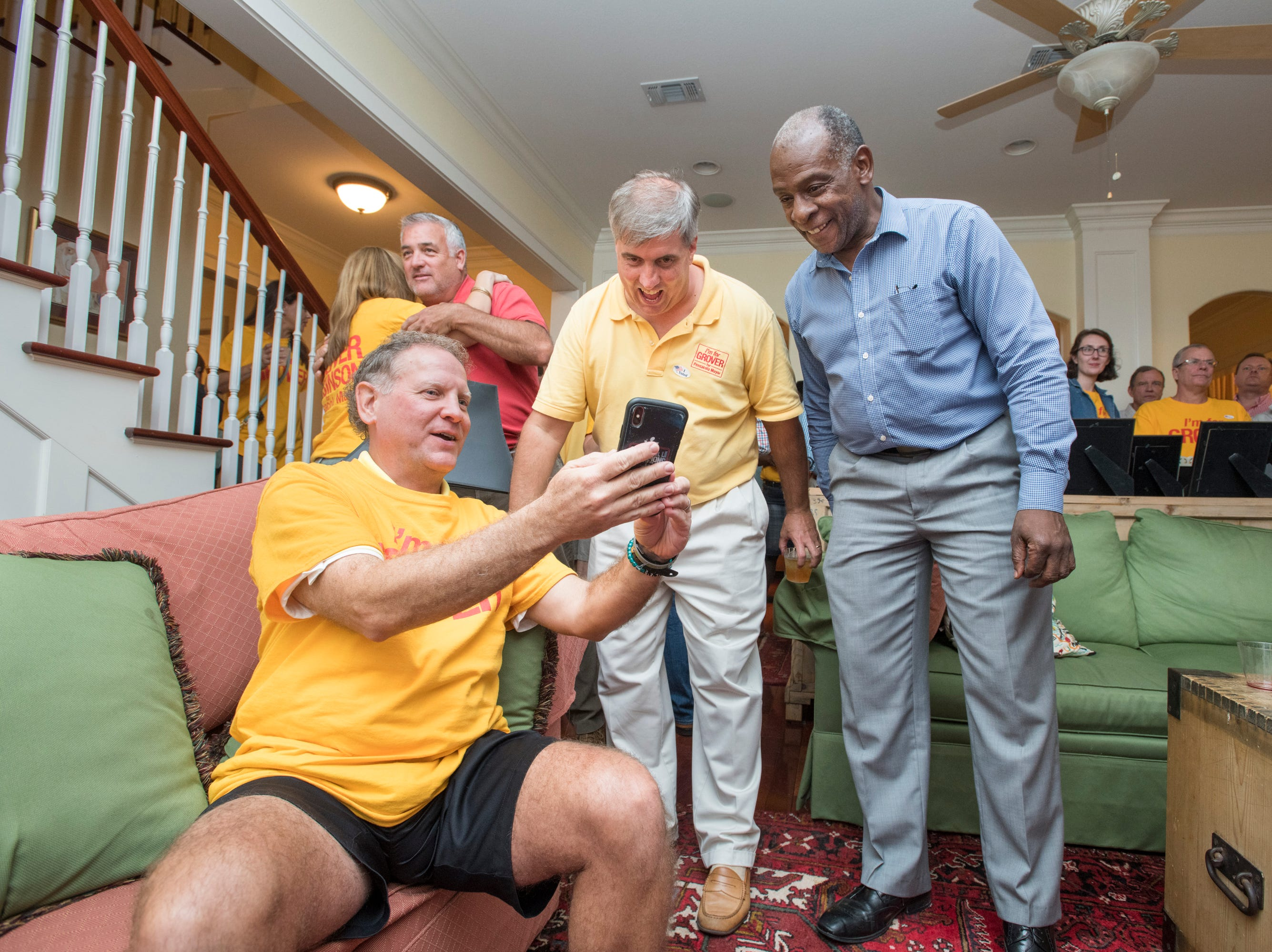 Grover Robinson, center, and supporters check the Penscola Mayoral race returns on Election Night in Pensacola on Tuesday, November 6, 2018.