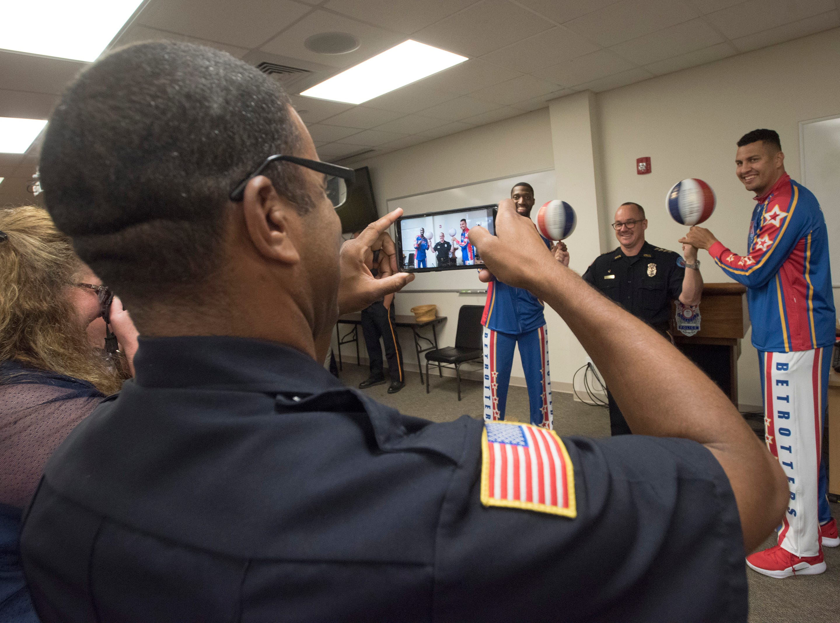 Bulldog Mack and El Gato Melendez, two members of the Harlem Globetrotters, teaches Pensacola Police chief Tommi Lyter as few tricks on Wednesday, Nov. 7, 2018.