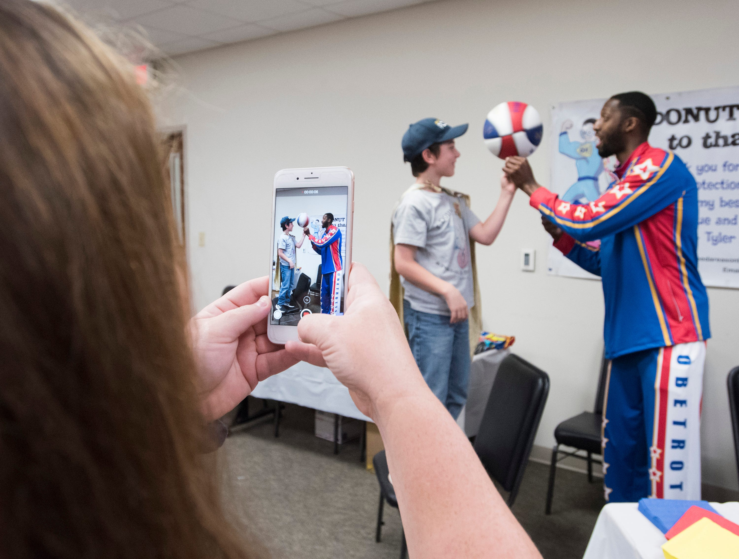 Sheena Carach records the moments Bulldog Mack, a member of the Harlem Globetrotters, teaches her son, Tyler Carach, a few tricks during his visit to the Pensacola Police Department on Wednesday, Nov. 7, 2018.