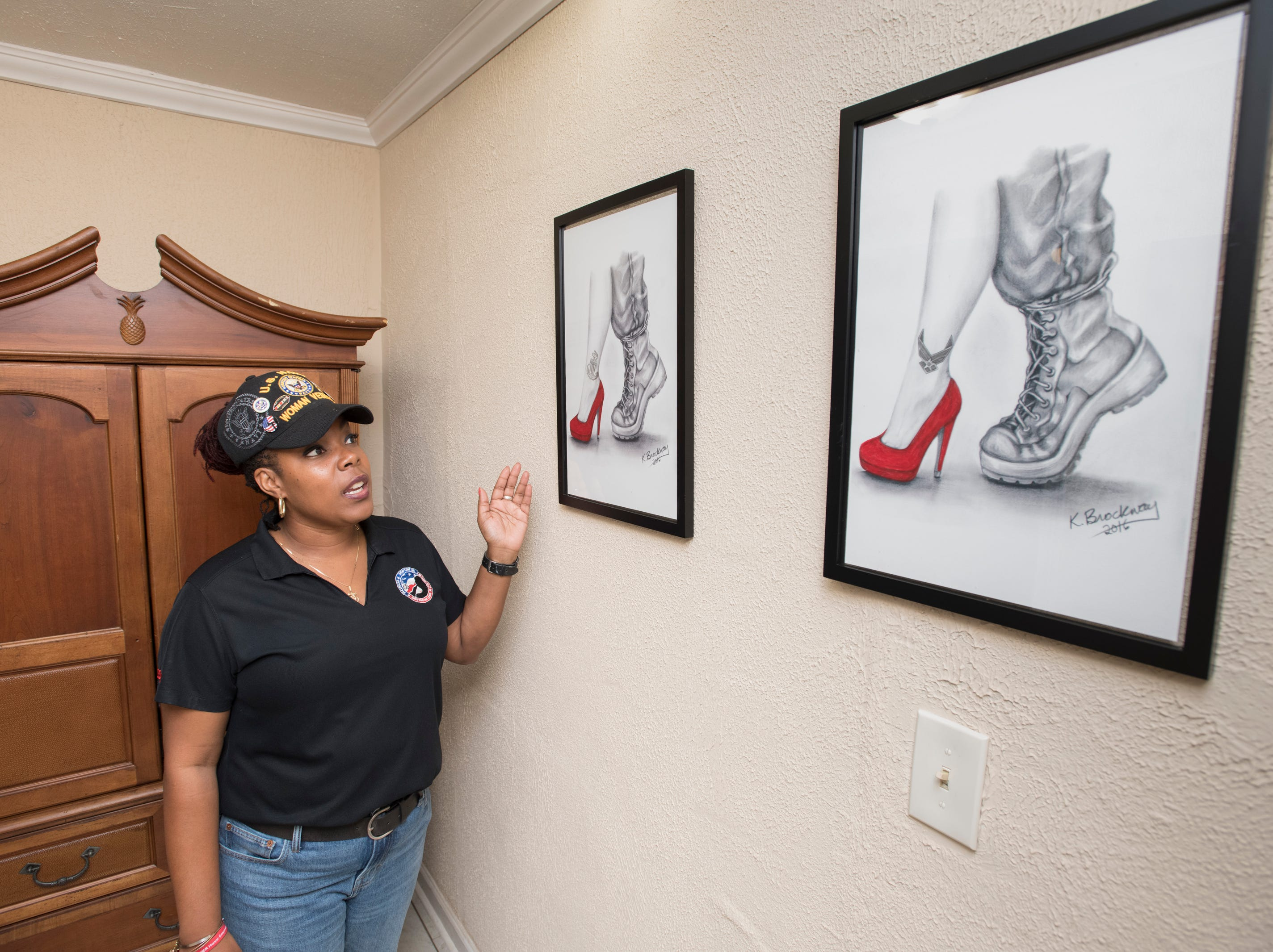 CEO and founder Nancy Bullock-Prevot talks about some of the artwork displayed at the HER Foundation Faith House on West Fairfield Drive in Pensacola on Wednesday, November 7, 2018.  These images are part of a collection showing the transition from the different branches of the military into civilian life for women.