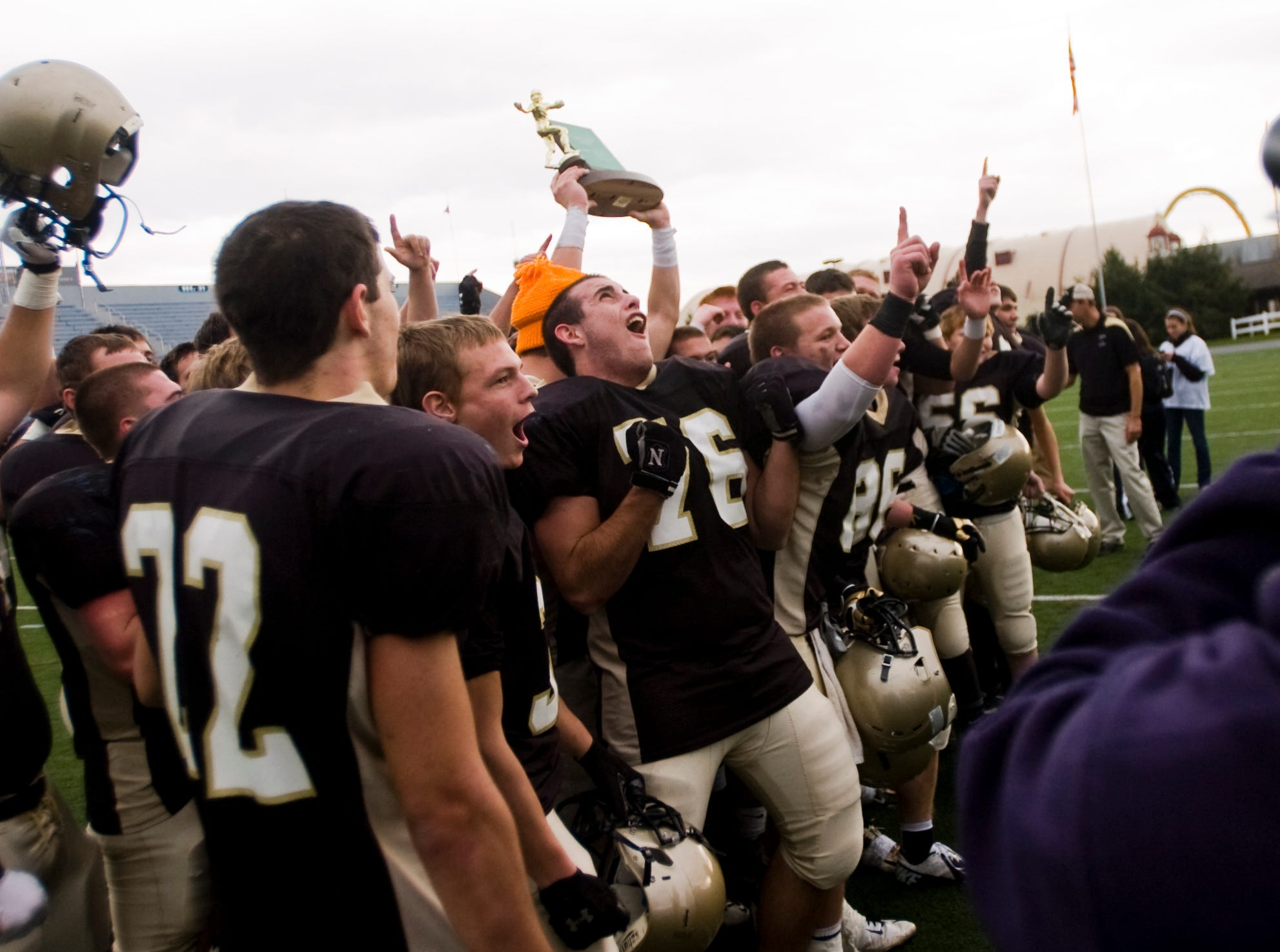In this file photo from 2012, Delone Catholic players celebrate with their trophy in front of TV cameras after their win against Steelton-Highspire in the District 3 Class A football championship on Friday at Hershey Stadium.