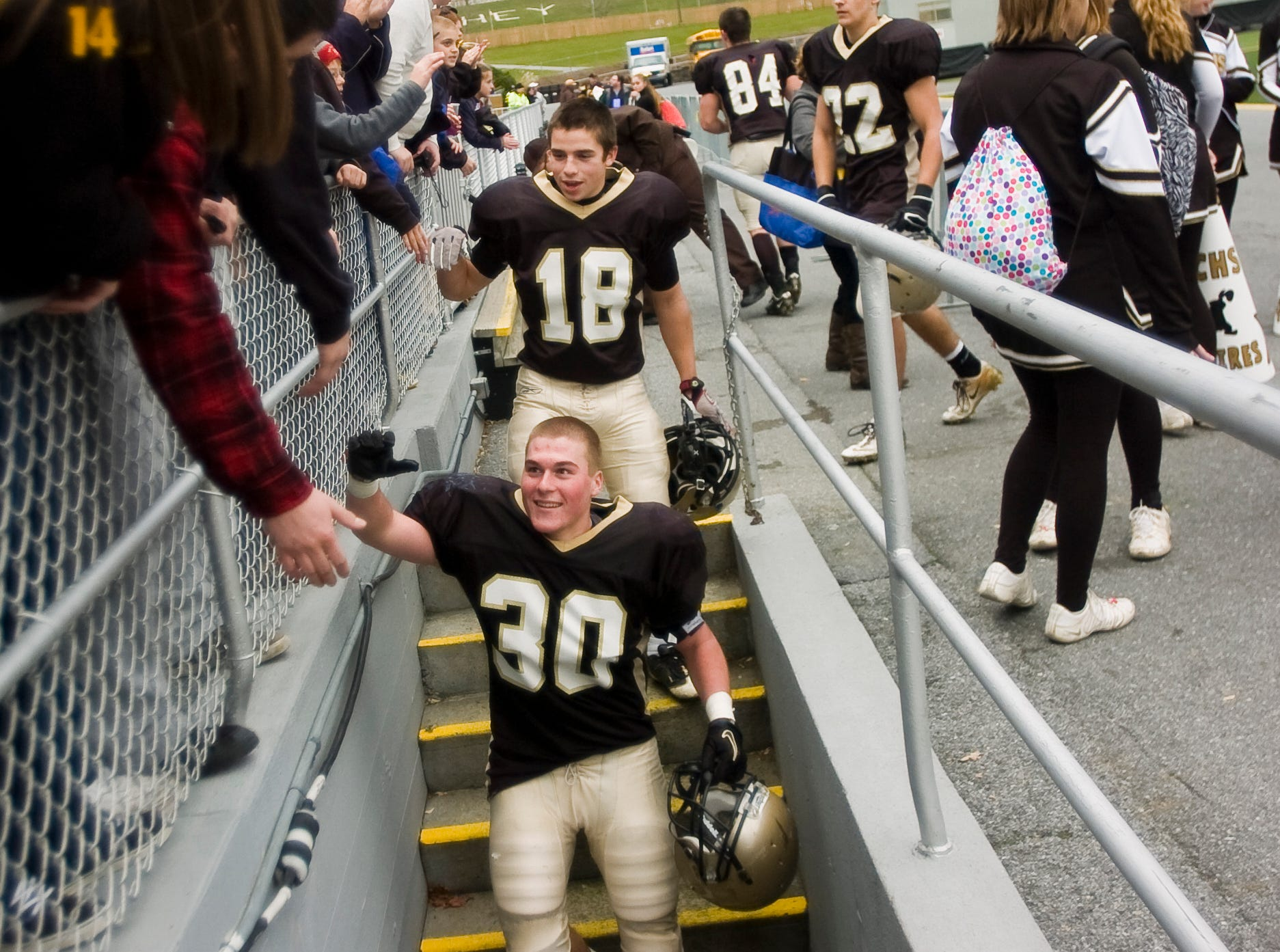 In this file photo from 2012, Delone's Tony Ward (18) and Hayden Bell (30) high five fans while heading back to the locker room at Hershey Stadium after their win against Steelton-Highspire in the District 3 Class A football championship on Friday.