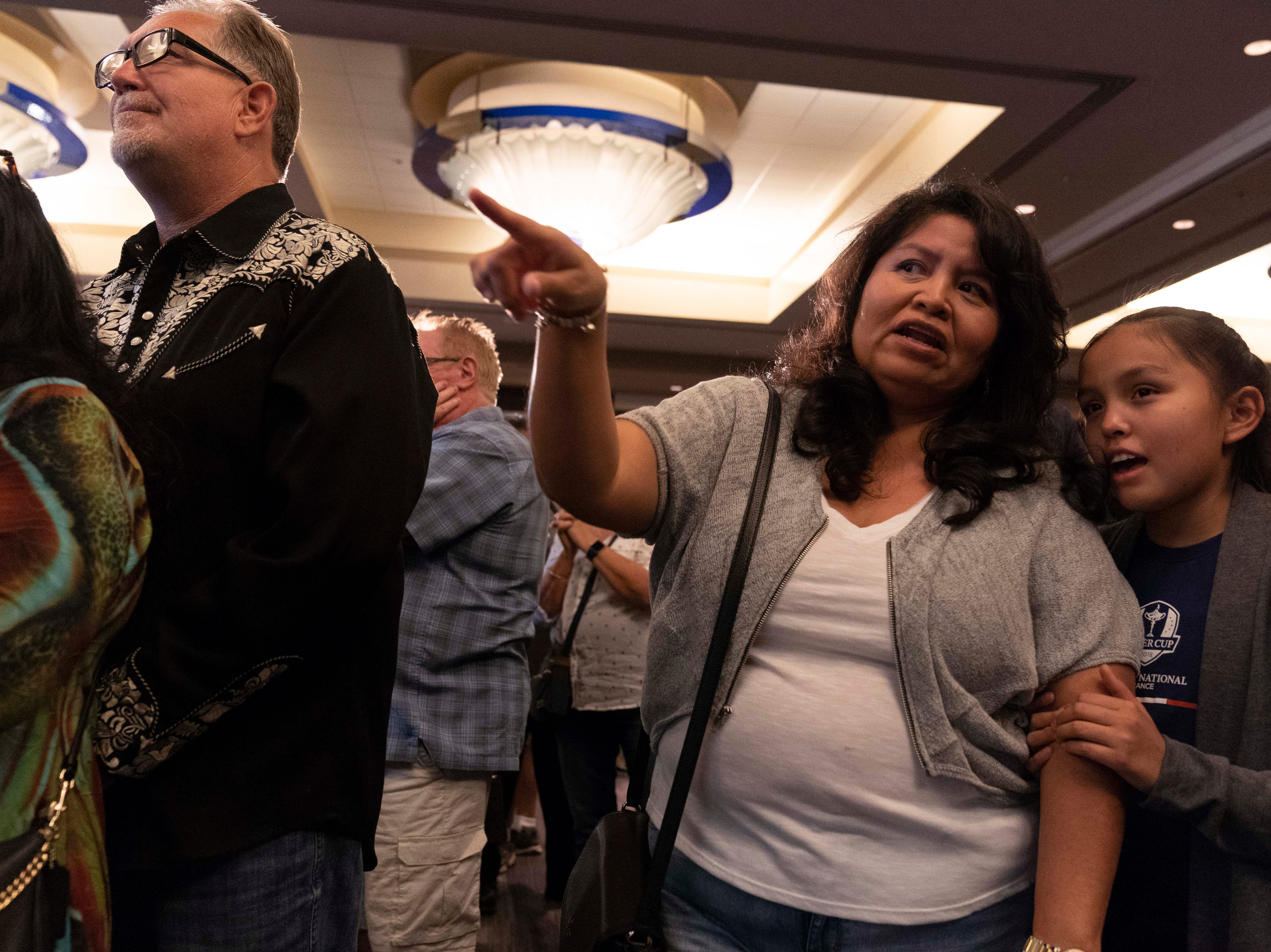 Democrat supporters Olivia Scott talks to her daughter Talon Watchman, 11, while others watch the national results on CNN at the Renaissance Phoenix Downtown Hotel on Nov. 6, 2018.