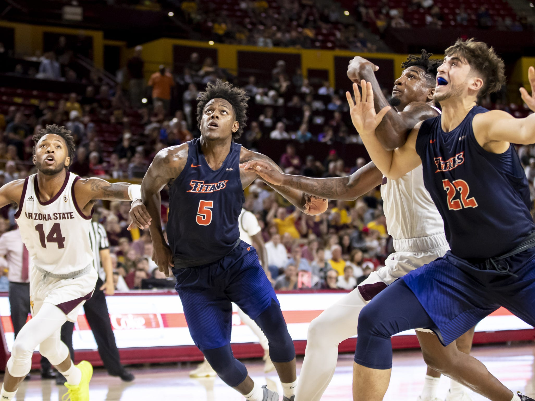 (L-R) Forward Kimani Lawrence (14) of the Arizona State Sun Devils, forward Davon Clare (5) of the Cal State Fullerton Titans, forward Romello White (23) of the Arizona State Sun Devils and forward Amel Kuljuhovic (22) of the Cal State Fullerton Titans look for a rebound at Wells Fargo Arena on Tuesday, November 6, 2018 in Tempe, Arizona.