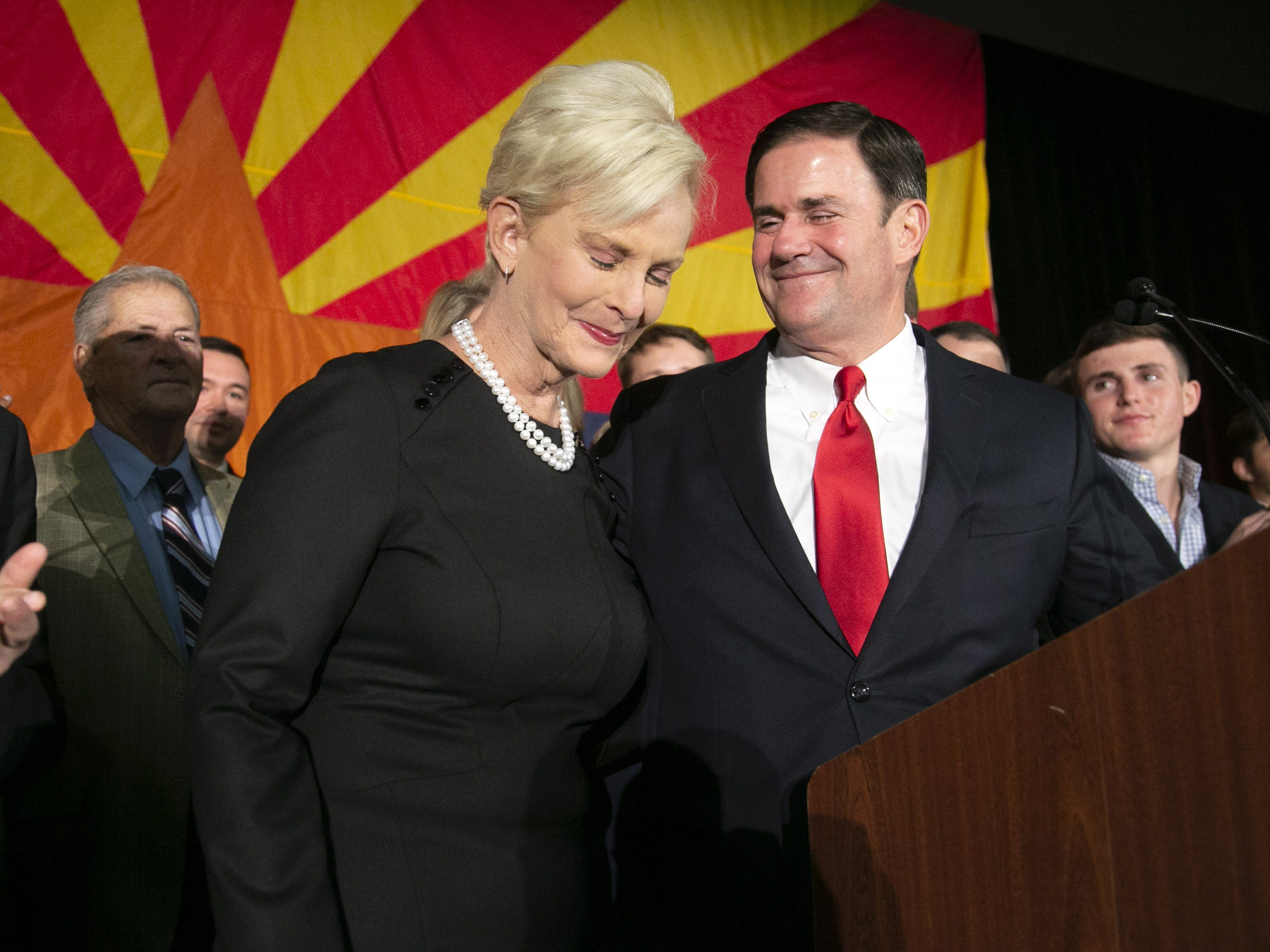 Gov. Doug Ducey speaks as Cindy McCain, the wife of the late Sen. John McCain looks on during the Republican watch party at the DoubleTree Resort in Scottsdale on Nov. 6, 2018.