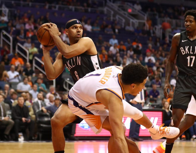 Former Suns guard Jared Dudley grabs a rebound in front of Devin Booker during the second half of a game Tuesday at Talking Stick Resort Arena.