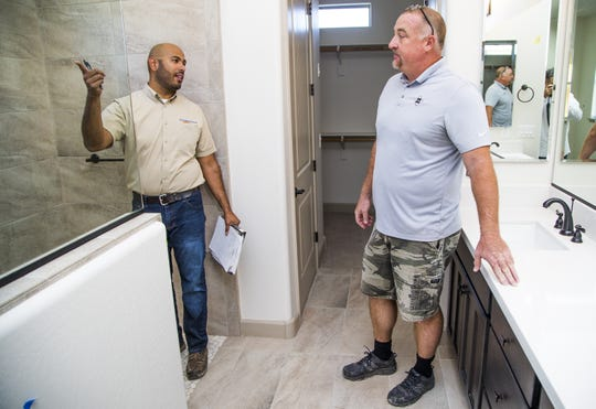 Rudy Del Rio (left) speaks with Drew Anderson of Southwest Residential Interiors inside a bathroom of a home under construction in the Verrado development.
