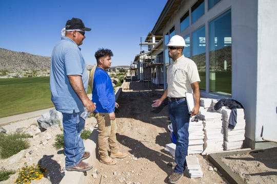 Rudy Del Rio (right) speaks with masons Ignacio Pineda (left) and Rafael Aguilar, in the backyard of a home under construction in the Verrado development.