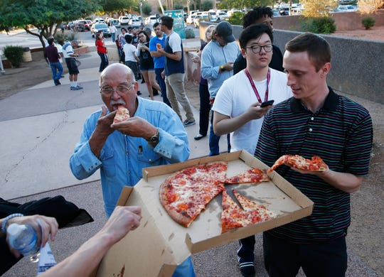 Rudy Rangel (left) and Bryan Mulloy help themselves to pizza while waiting in line to vote at the Tempe History Museum in Ariz. Nov. 6, 2018. An anonymous person bought pizza for people in line.