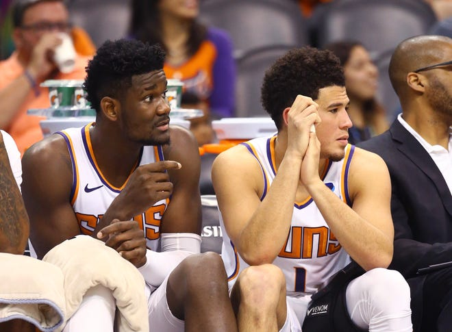 Deandre Ayton and Devin Booker look on from the bench during the second half of the Suns' loss to the Nets on Tuesday at Talking Stick Resort Arena.