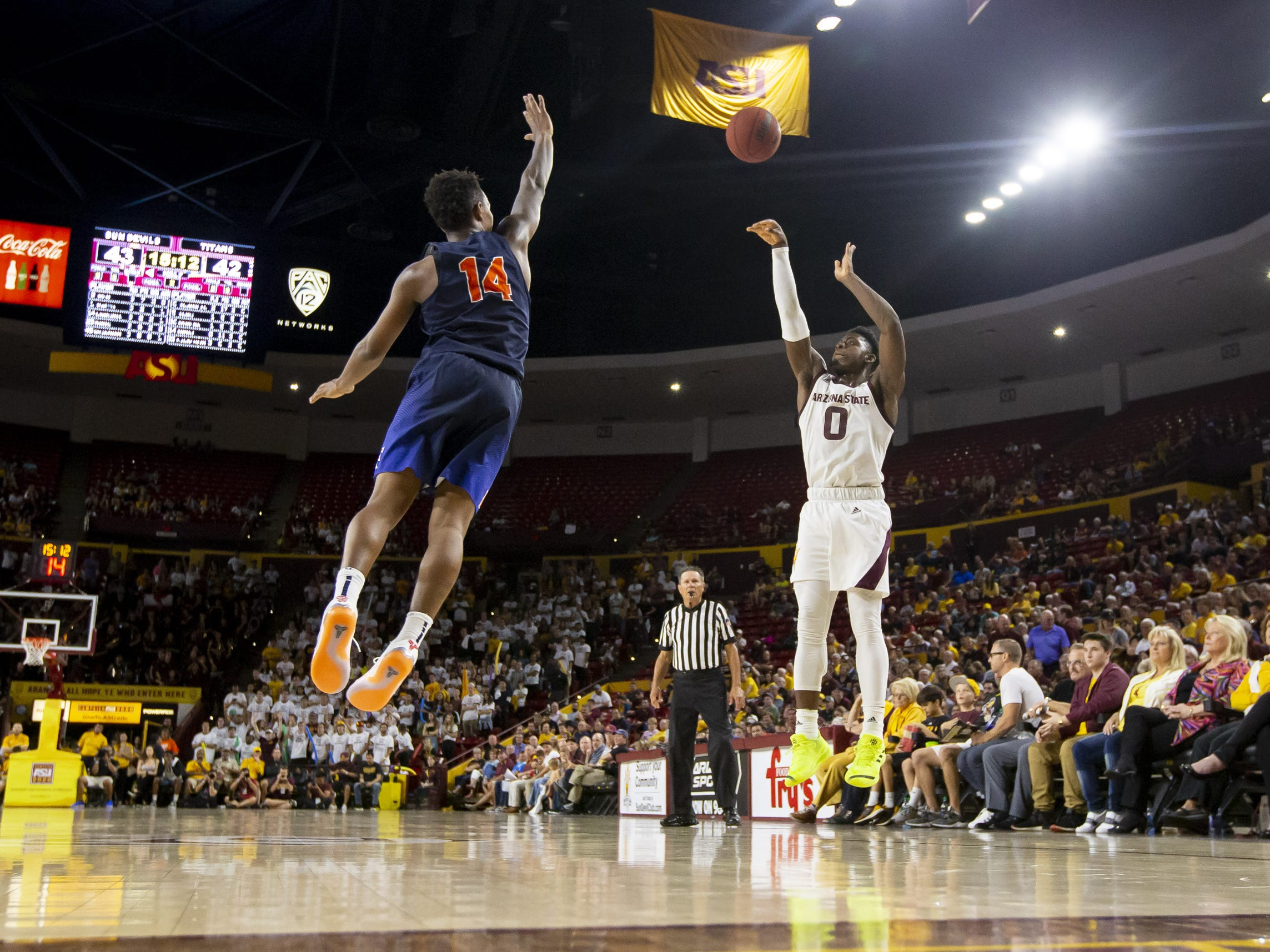 Guard Luguentz Dort (0) of the Arizona State Sun Devils shoots a three-pointer against guard Khalil Ahmad (14) of the Cal State Fullerton Titans at Wells Fargo Arena on Tuesday, November 6, 2018 in Tempe, Arizona.