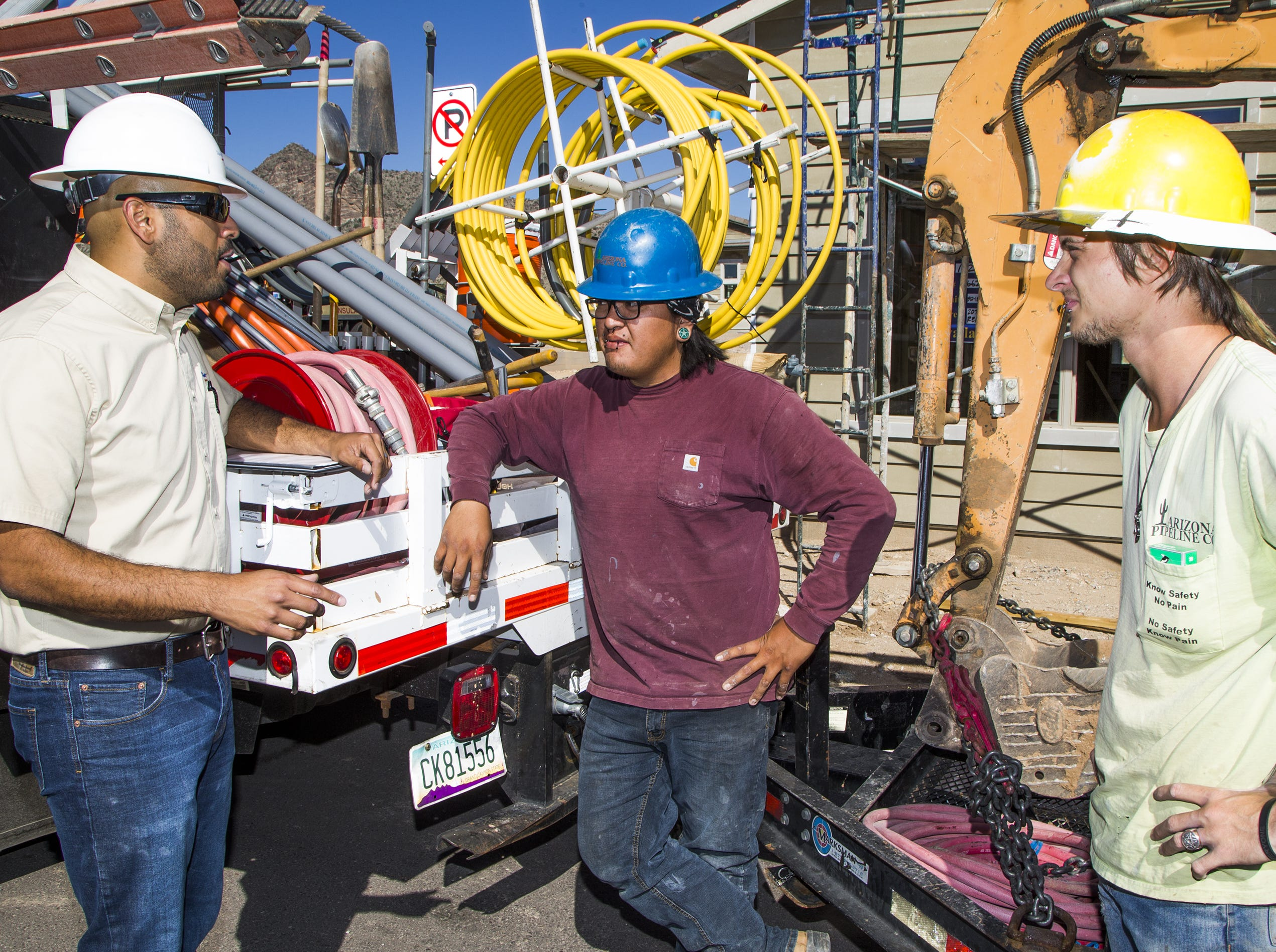 Rudy Del Rio (left) a builder with David Weekley Homes, speaks with MacKenzie Manygoats (middle) and Joshua Willis of Arizona Pipeline Company during installation of gas and electric lines in the Verrado development in Buckeye Nov. 5, 2018.