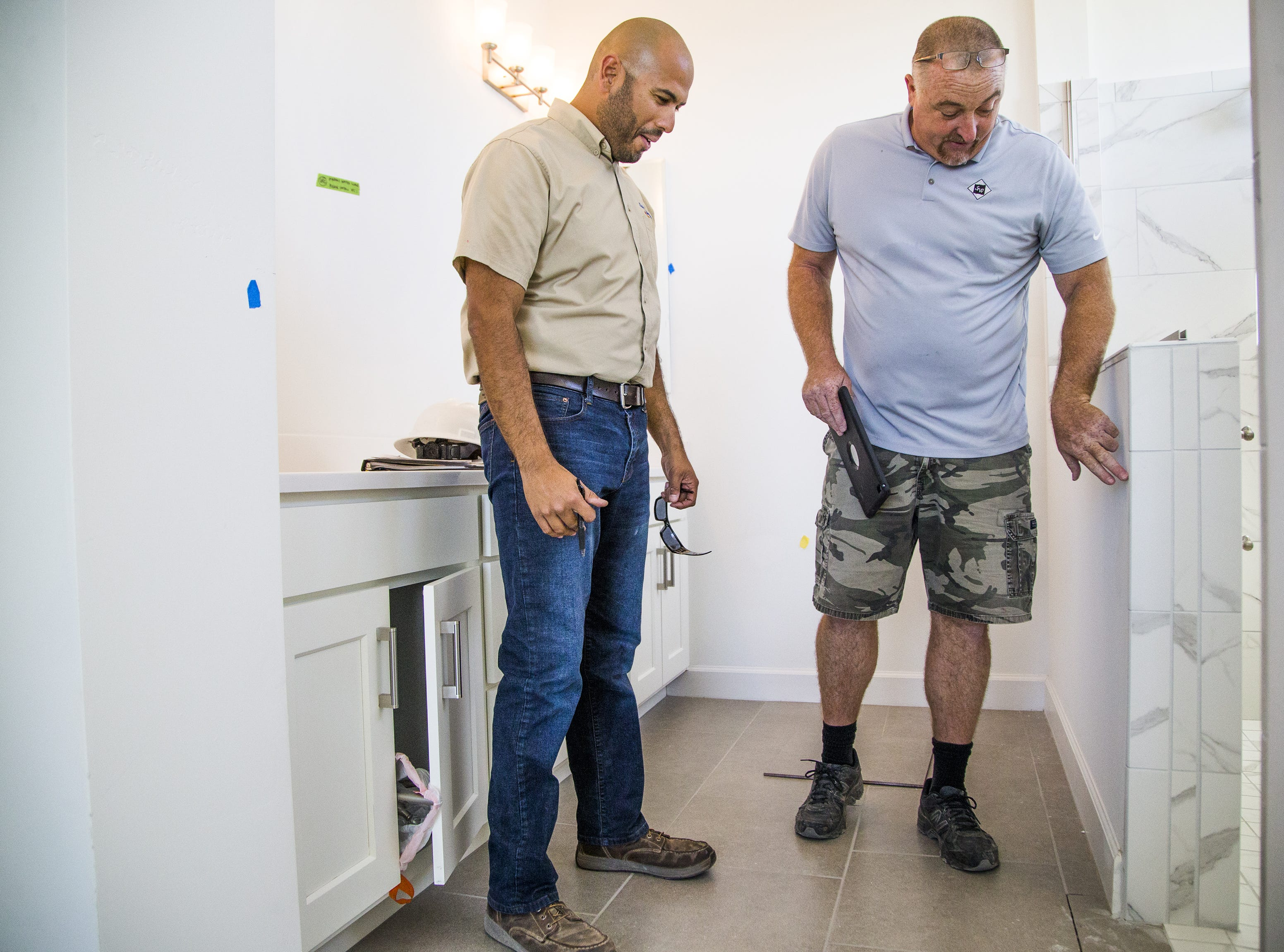 Rudy Del Rio, left, a builder with David Weekley Homes, speaks with Drew Anderson of Southwest Residential Interiors inside a bathroom of a home under construction in the Verrado development in Buckeye, Monday, November 5, 2018.