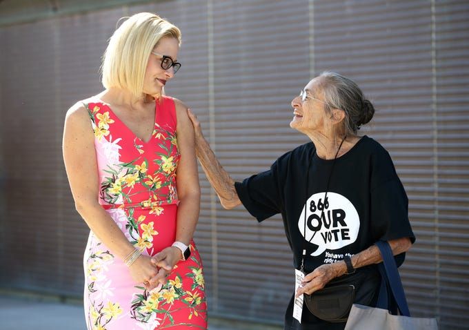 Rep. Kyrsten Sinema, D-Ariz., the Democratic candidate for the U.S. Senate talks with Rivko Knox outside a polling center on Nov. 6, 2018 at the Burton Barr Central Library in Phoenix, Ariz. Sinema is running against Republication Martha McSally.