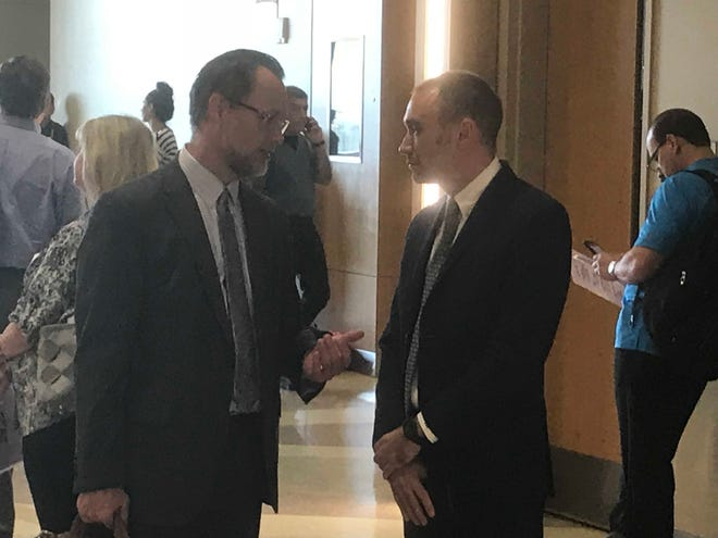 Daniel K. Hughes, former CEO of Discovery Creemos Academy (right), talks with his lawyer, Kurt Altman, on Nov. 7, 2018, in Maricopa County Superior Court.