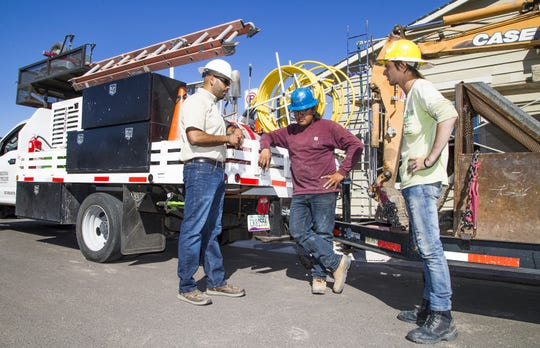 Rudy Del Rio (left), a builder with David Weekley Homes, speaks with MacKenzie Manygoats (middle) and Joshua Willis of Arizona Pipeline Company during installation of gas and electric lines.