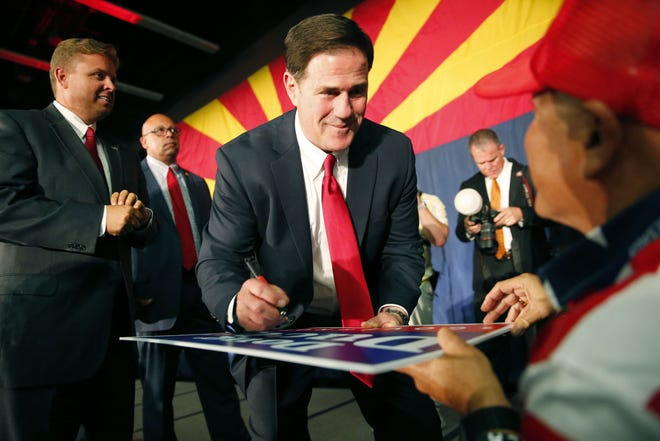 Gov. Doug Ducey signs an autograph for a supporter during the Arizona Republican Party Election Night party in Scottsdale, Ariz. Nov. 6, 2018. Ducey is won his re-election against Democratic challenger David Garcia.
