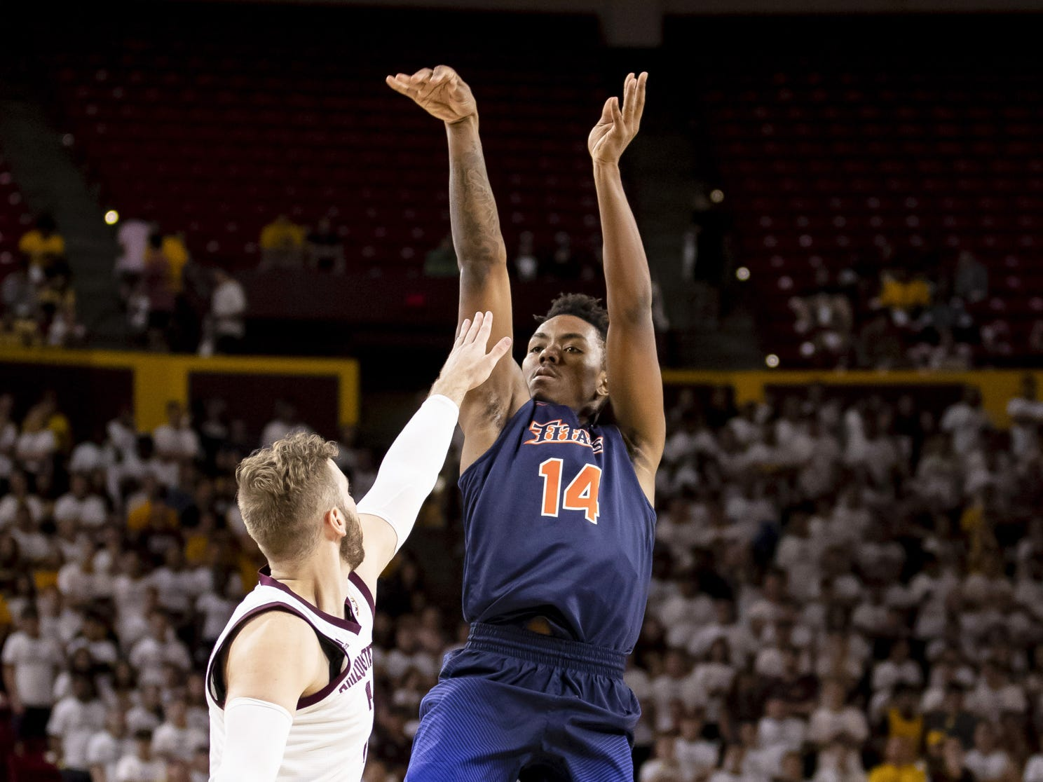 Guard Khalil Ahmad (14) of the Cal State Fullerton Titans shoots against forward Mickey Mitchell (3) of the Arizona State Sun Devils at Wells Fargo Arena on Tuesday, November 6, 2018 in Tempe, Arizona.