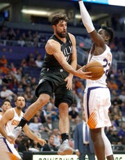 Brooklyn Nets forward Joe Harris (12) passes the ball around Phoenix Suns center Deandre Ayton during the first half of an NBA basketball game Tuesday, Nov. 6, 2018, in Phoenix. (AP Photo/Rick Scuteri)
