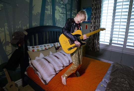 Vedder Gabriel, 10, of Peoria, playing guitar on his bed.