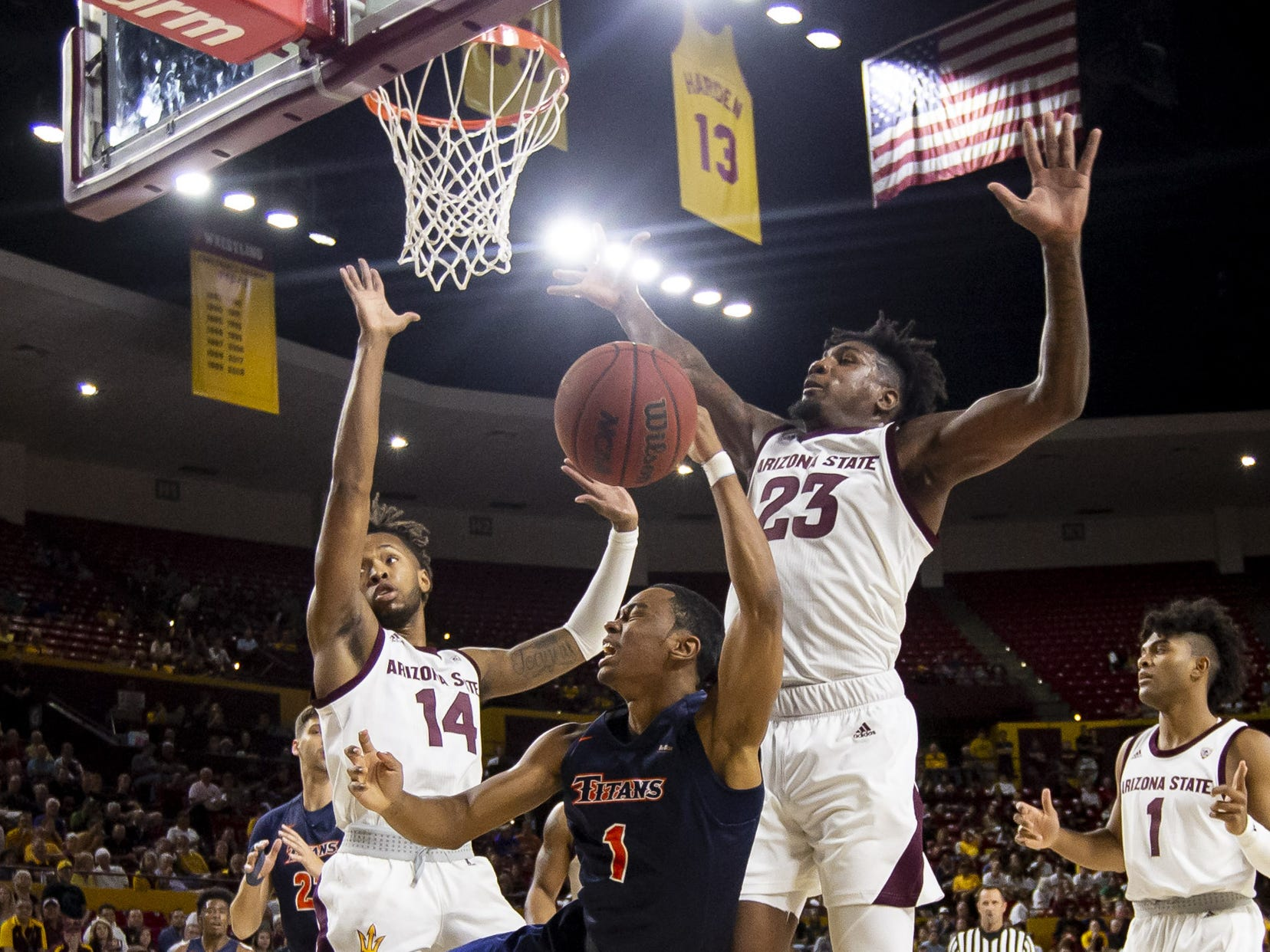 Guard Jamal Smith (1) of the Cal State Fullerton Titans shoots against forward Kimani Lawrence (14) and forward Romello White (23) of the Arizona State Sun Devils at Wells Fargo Arena on Tuesday, November 6, 2018 in Tempe, Arizona.