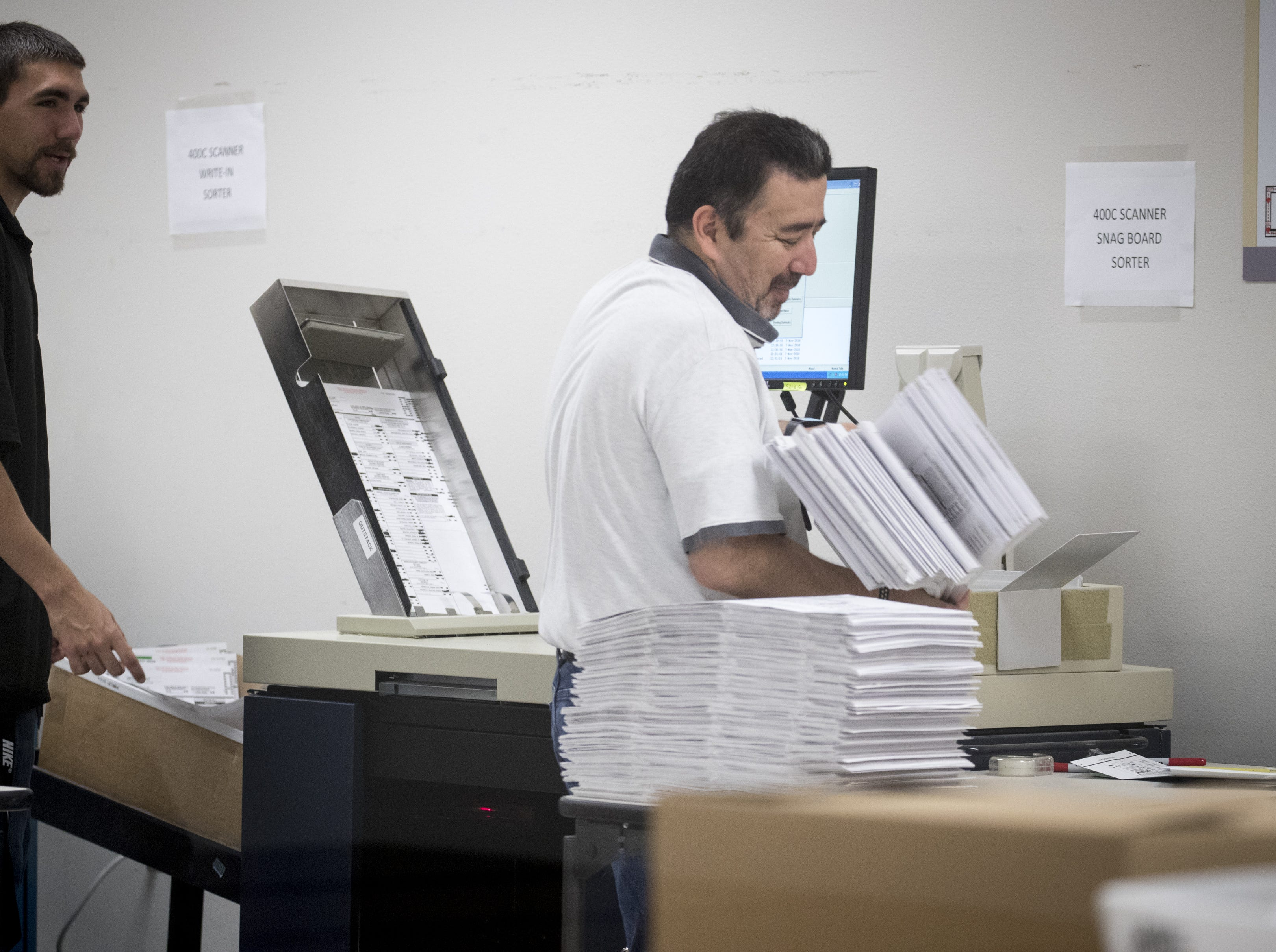 Gary Ramirez (right) processes ballots on Nov. 7, 2018, at the Maricopa County Tabulation and Election Center, 510 S. 3rd Ave., Phoenix.