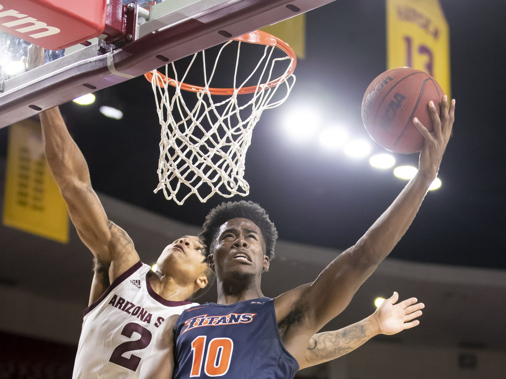 Guard Austen Awosika (10) of the Cal State Fullerton Titans drives to the basket against Rob Edwards (2) of the Arizona State Sun Devils at Wells Fargo Arena on Tuesday, November 6, 2018 in Tempe, Arizona.
