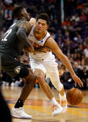 Phoenix Suns guard Devin Booker (1) is fouled by Brooklyn Nets guard Caris LeVert during the second half of an NBA basketball game Tuesday, Nov. 6, 2018, in Phoenix. The Nets won 104-82. (AP Photo/Rick Scuteri)