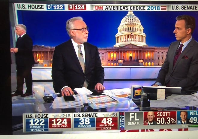 CNN's John King works in the background as Wolf Blitzer and Jake Tapper talk about election returns on election night.