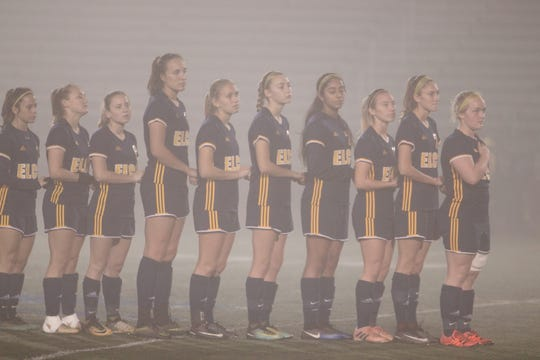 The starters for the Elco girls soccer team stand together in the fog as the National Anthem is played