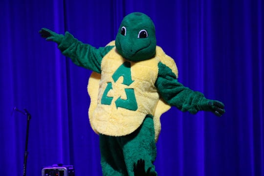 """""""Myrtle"""" the Recycling Turtle, mascot for the Ottawa Sandusky Seneca Solid Waste District, dances the morning away during the Earth Jam concert in Port Clinton."""