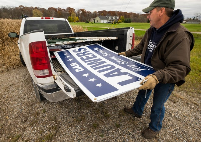 Dan Lauwers loads a campaign sign into the back of his truck Wednesday, Nov. 7, 2018 in North Street. Lauwers, who previously termed-out of his role in the state House's 81st District, was elected as 25th District state senator during Tuesday's mid-terms.