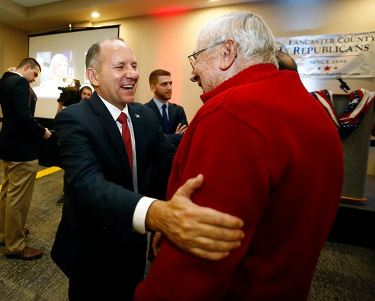 U.S. Rep. Lloyd Smucker, R-Pa., left, celebrates with supporter Ira Groff, of Leola, after winning re-election for the Pennsylvania 11th congressional district, at Spooky Nook Sports Complex in Manheim, Pa., Tuesday, Nov. 6, 2018. (AP Photo/Chris Knight)
