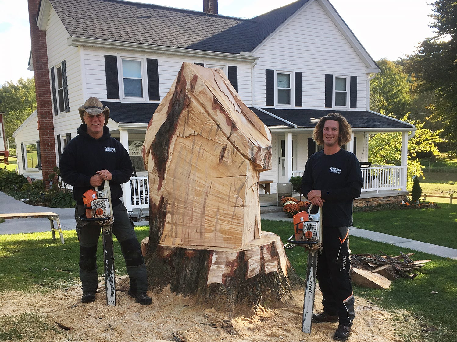 Paul Walco, left, and his son Austin begin trimming the trunk of the old Silver Maple creating the fairy house at the Teaching Museum for the Fiber Arts & Textiles near Winterstown. The business Chainsaw Carving by Paul is based near Jacobus.