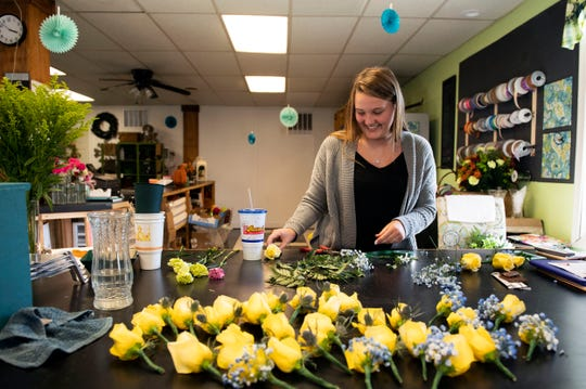Hayden Grimes, 18, works in her parents' floral shop, Fawn Grove Florist and Gifts, Thursday, Oct. 18, 2018. 'There are still people who live in Fawn Grove that don't know it is here,' Hayden said of the complex that also includes an auto mechanic shop, a brewery, tattoo parlor and a cafe.