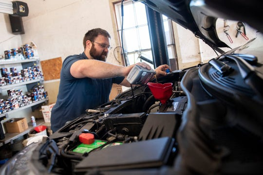 Chris Heaps pours oil into a car during a routine oil change at his shop, South County Auto, in Fawn Grove, Thursday, Oct. 18, 2018. Chris and his brother, J.R., who owns South County Brewing, have been operating their own businesses side-by-side for nearly the past decade.