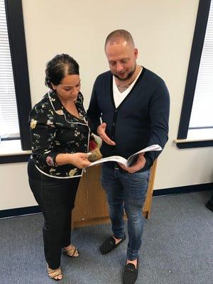 Keila Rosado, community liason for the new Pennsylvania Preparatory Academy, and founder Brandon Marquette review some curriculum.
