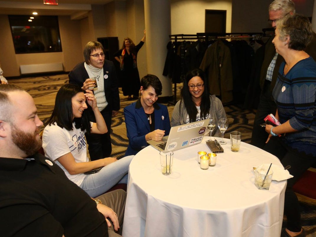 Jamie Romeo, center, checks returns at the Democratic gathering on Election night at the Hyatt Regency Rochester.