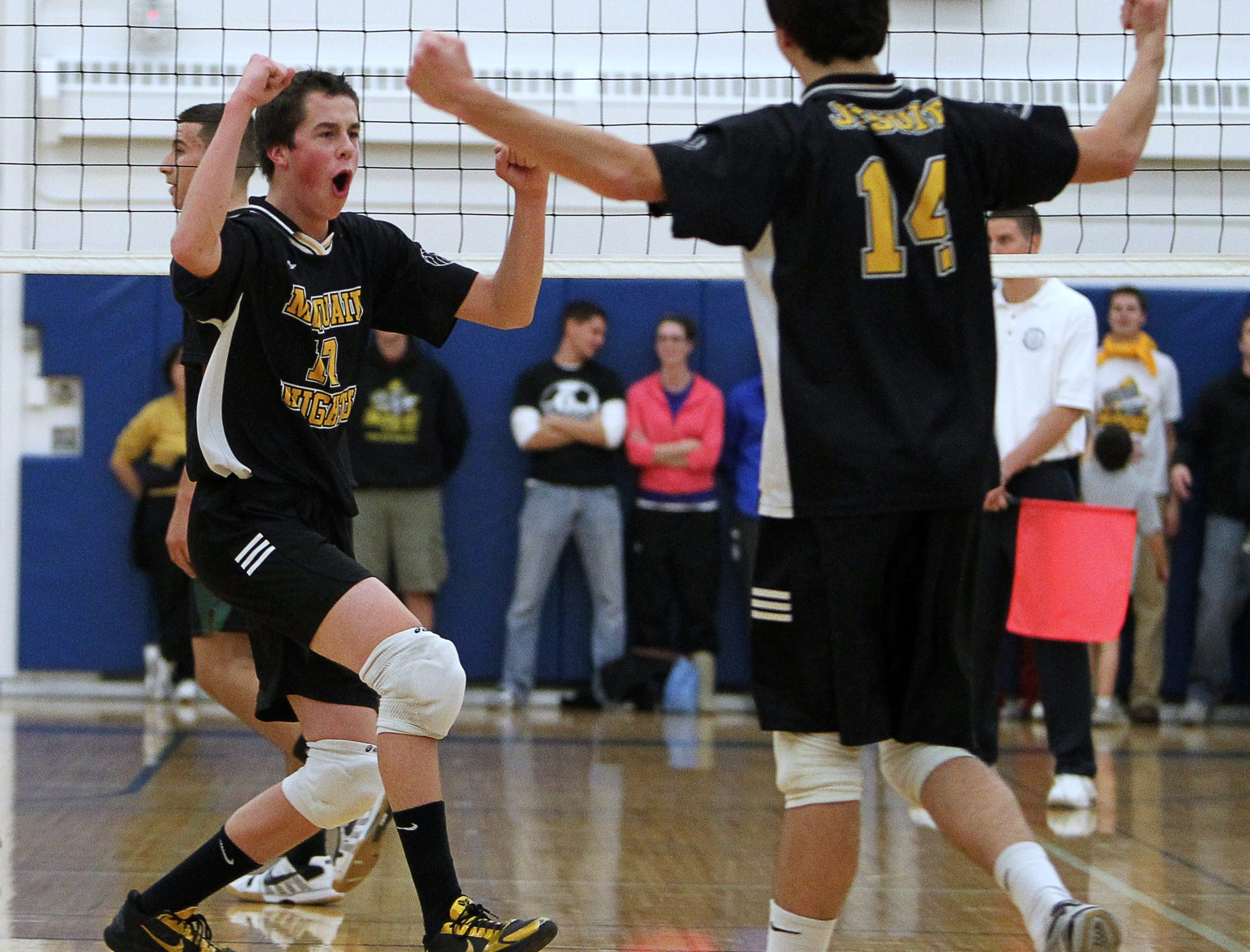 McQuaid's Steve O'Dell, left, celebrates a point with teammate Michael Desino, right, during a volleyball match at Webster Schroeder on Nov. 10, 2010.