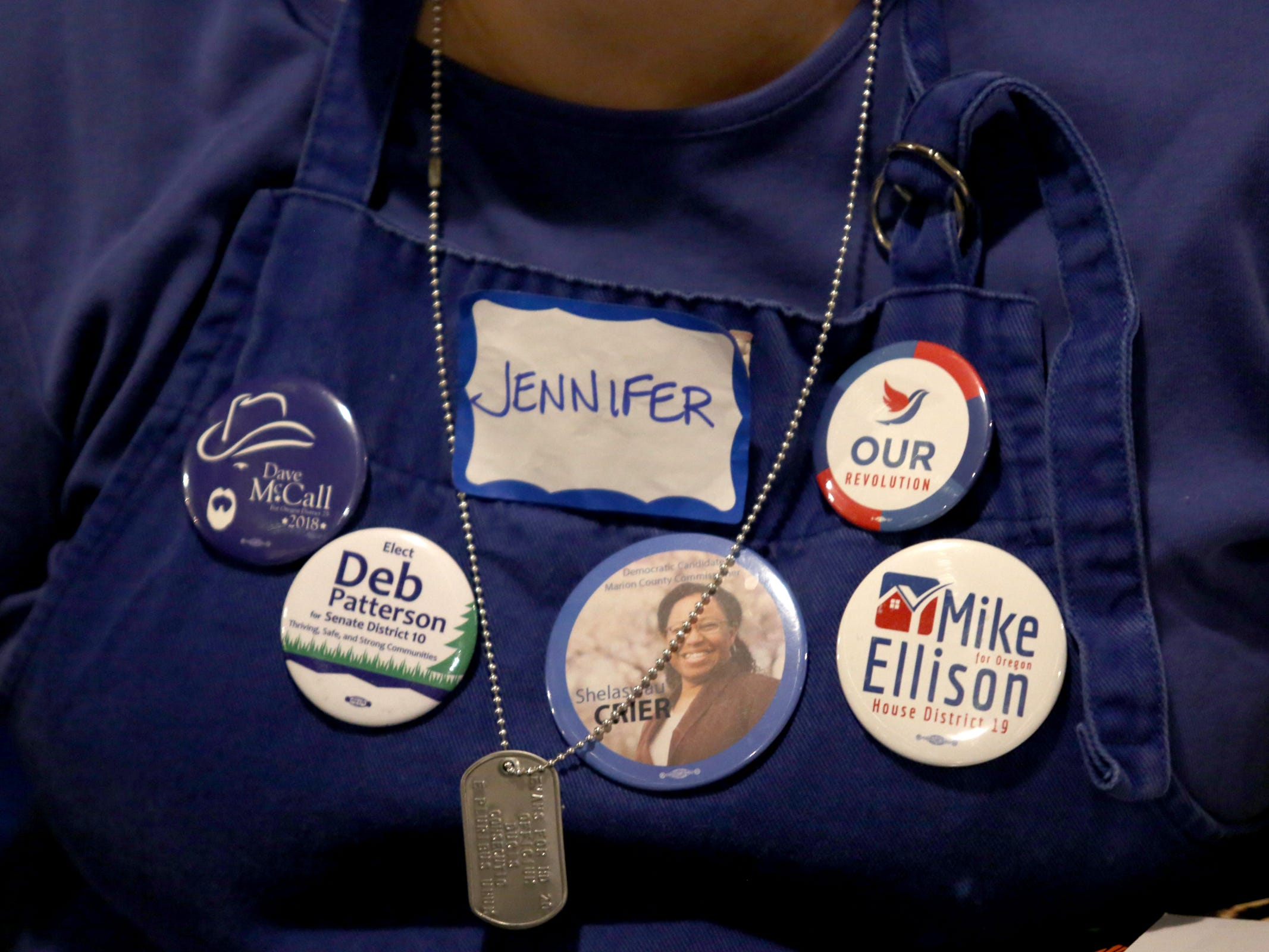 Jennifer Sprague, of Salem, wears candidate buttons during an election night party hosted by Marion County Democrats and Polk County Democrats at the Willamette Heritage Center in Salem on Tuesday, Nov. 6, 2018.