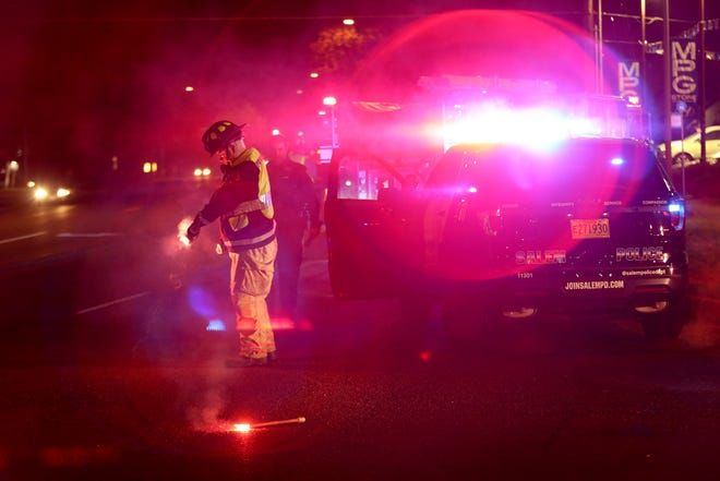 A Salem firefighter puts out road flares on Mission St. SE near Hines St. SE following the stop of a hit-and-run driver following a two-vehicle crash at 12th St. SE and Mission St. SE in Salem on Tuesday, Nov. 6, 2018.