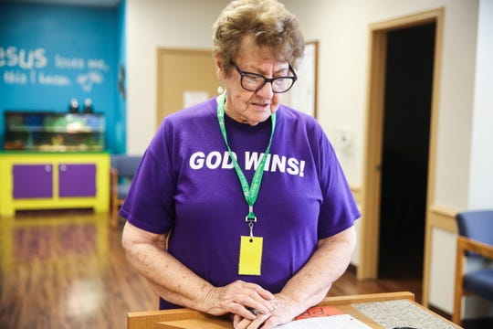 Jeorgia Brassell, volunteer, looks down a list of people helped with clothes, food and household Wednesday, Nov. 7, 2018, at Rust Street Ministries.