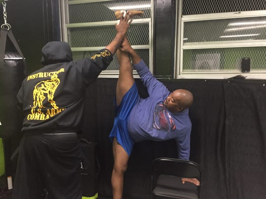 Charles Baines stretches during a workout with his conditioning coach Andre Tyler in Onancock, Virginia on Tuesday, Nov. 6, 2018.