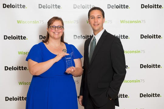 Senior Business Analyst Amanda Radloff and Paul Miller, manager - communications, receive the Deloitte Wisconsin 75 award on behalf of Acuity.